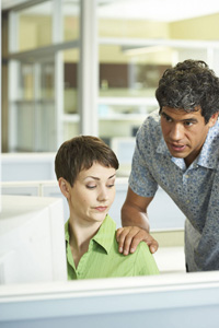 Man grabing shoulder of female co-worker